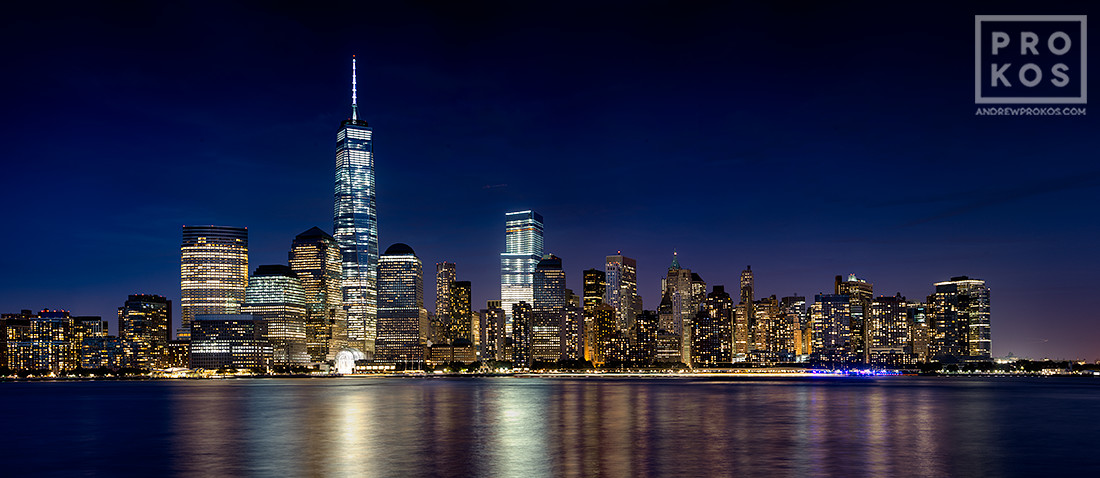 A panoramic skyline of Lower Manhattan NYC, the Hudson River, and the World trade Center at night as seen from New Jersey