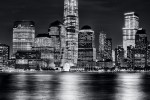 A black and white photograph of Lower Manhattan, Hudson River, and the World Trade Center at night, New York City