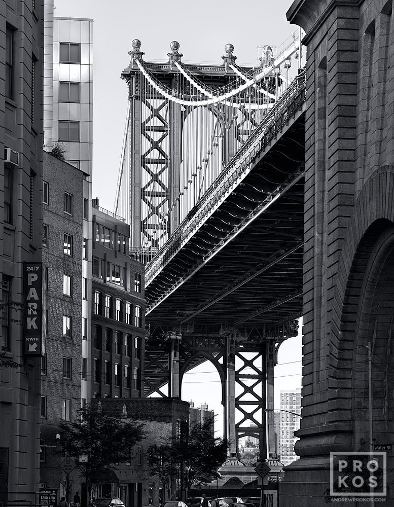 A black and white street view of the manhattan bridge as seen from downtown brooklyn