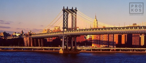 A color fine art photo of the Manhattan Bridge and East River at sunset, New York City