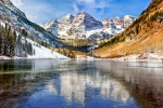 A high-definition landscape photo of the Maroon Bells mountain range in winter reflected on the frozen surface of Maroon Lake, near Aspen, Colorado.