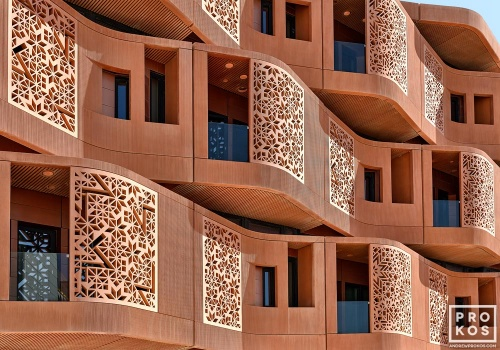 An architectural photo of the undulating terracotta facade of the Masdar Institute in Abu Dhabi, UAE