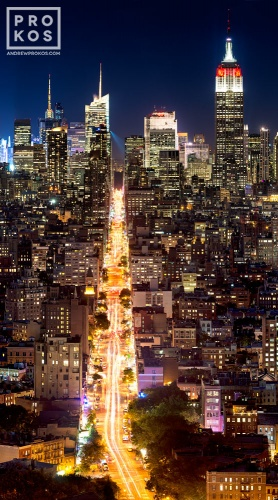 A vertical cityscape photograph of New York City at night as seen from SoHo