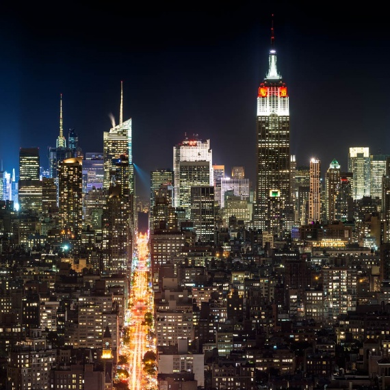 A panoramic skyline of the buildings of Midtown Manhattan, and the Empire State Building at night. PHOTO ID: COLNYCMIDPANNT-1327