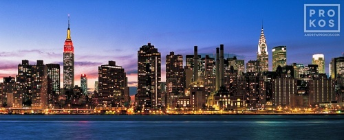 A panoramic view of New York City, the Empire State Building, and the East River at dusk