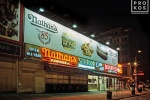 A street scene photo of Nathan's Famous restaurant at night in Coney Island, Brooklyn