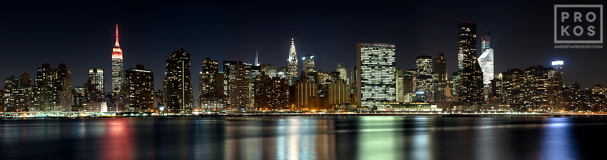 A wide panoramic skyline photograph of Midtown Manhattan at night, New York City.