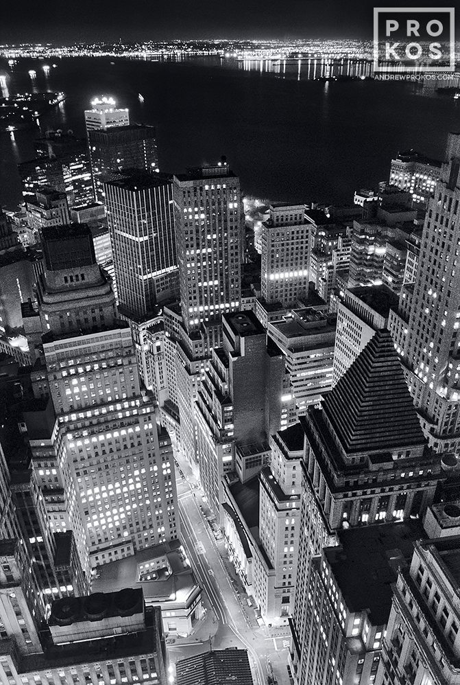 A black and white aerial view of the skyscrapers of Lower Manhattan and New York Harbor at night