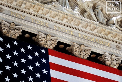 An architectural detail photo from the facade of the New York Stock Exchange (NYSE) facade draped in an American flag