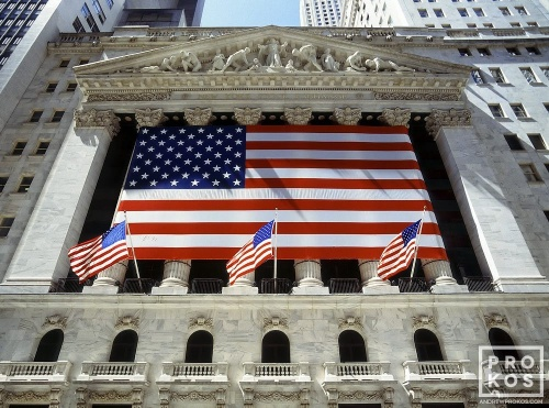 An architectural exterior photo of the New York Stock Exchange (NYSE) draped with American flags