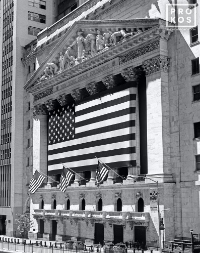 A black and white fine art photo of the New York Stock Exchange exterior with American flags