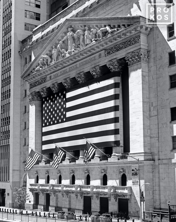 A black and white large format fine art photograph of the New York Stock Exchange (NYSE) with American flags