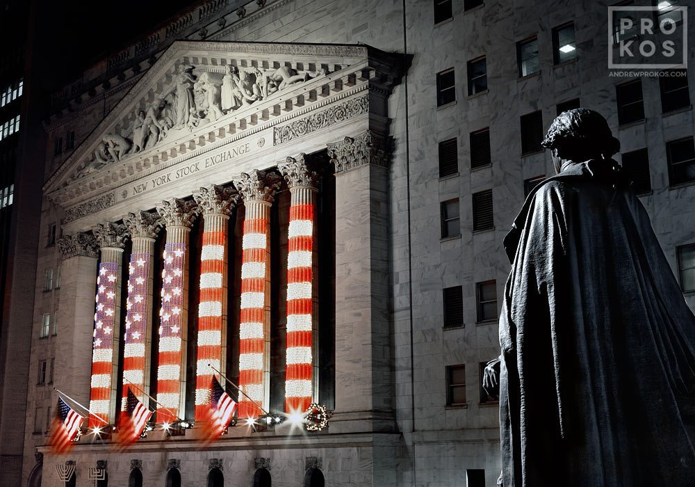 An architectural fine art photo of the New York Stock Exchange (NYSE) and statue of George Washington at night from Federal Hall
