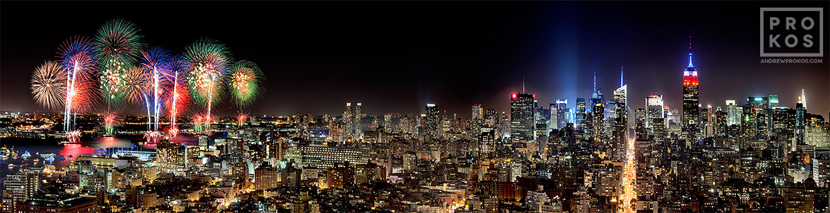 A panoramic long-exposure cityscape photo of the New York City skyline at night with fireworks on the Fourth of July.