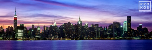 A panoramic skyline photo of New York City, the Empire State Building, and the Chrysler Building from Brooklyn at dusk