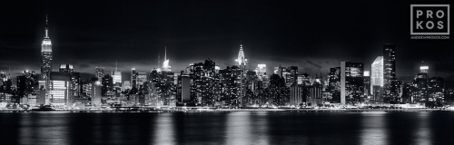 A panoramic long-exposure skyline of New York City at night in black and white.
