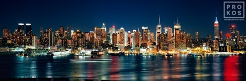 A panoramic skyline photo of New York City as seen from Weehawken, New Jersey at night