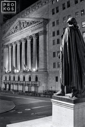 A fine art photo of the New York Stock Exchange (NYSE) and statue of George Washington at Federal Hall on Wall Street at night