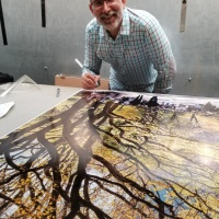 """Photographer Andrew Prokos signing a 60"""" limited edition print of Poet's Walk in Autumn"""