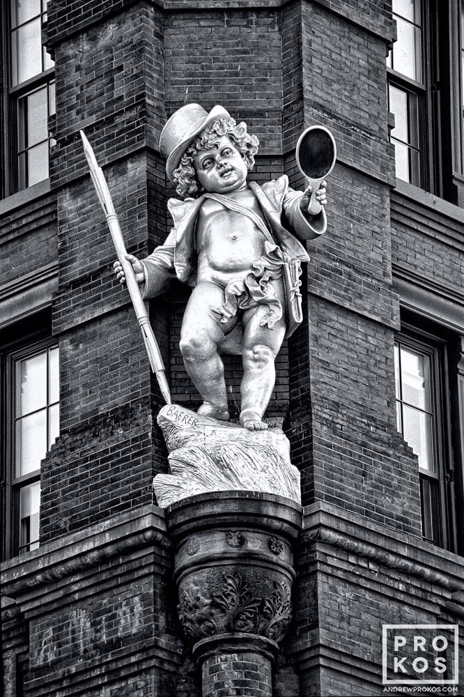 A fine art architectural photo of the statue of Puck on the facade of the Puck Building, NYC in black and white
