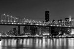 A black and white panoramic photo of the Queensboro Bridge and New York City skyline at night