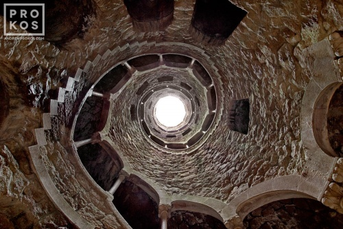 The Poco Iniciatico, a hidden well with arched spiral stairway in the Quinta da Regaleira gardens of Sintra, Portugal