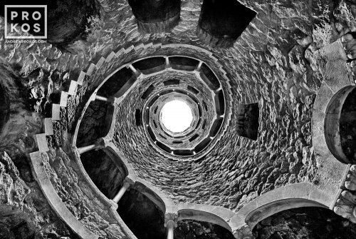 A black and white view of the Poco Iniciatico, a hidden well with arched spiral stairway in the Quinta da Regaleira gardens of Sintra, Portugal