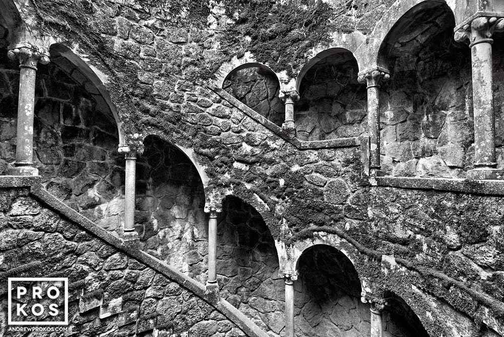 The Poco Iniciatico, a hidden well with arched spiral stairway in the Quinta da Regaleira gardens of Sintra, Portugal captured in black and white
