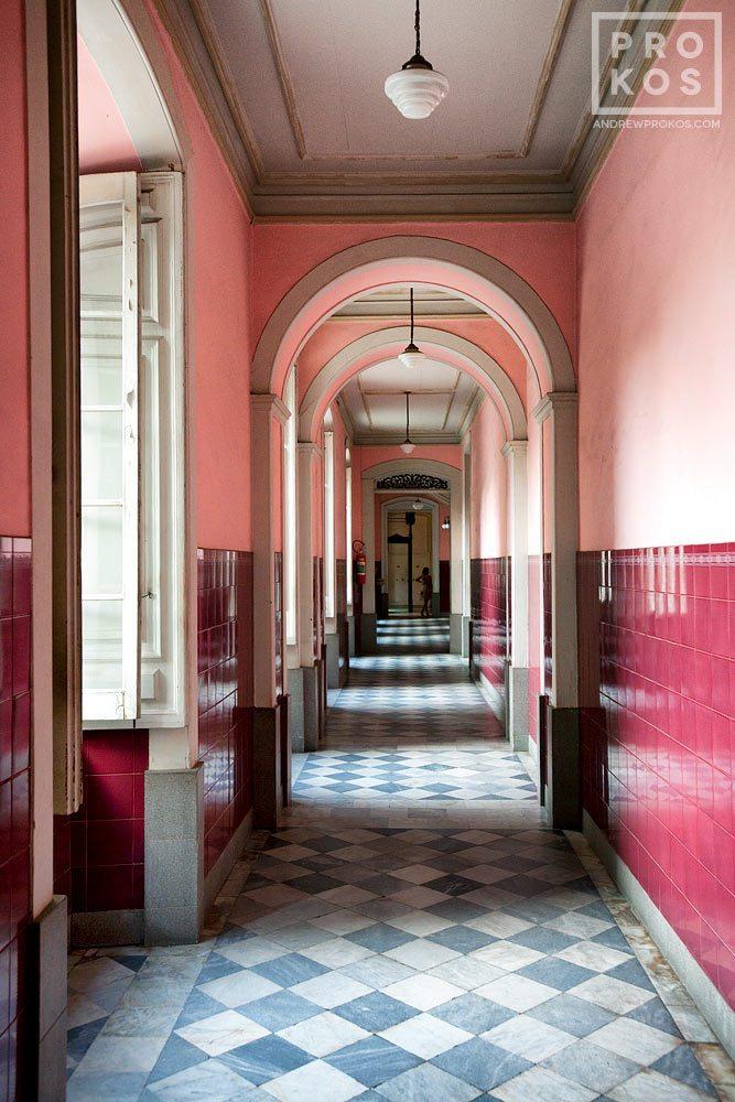 A fine art architectural photo of an interior in shades of pink and maroon, in Rio de Janeiro's Centro Historico. Um corredor em tons de rosa e marrom, no Centro Histórico do Rio de Janeiro.
