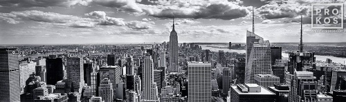 A black and white panoramic cityscape photo of New York City and the Empire State Building as seen from Rockefeller Center.