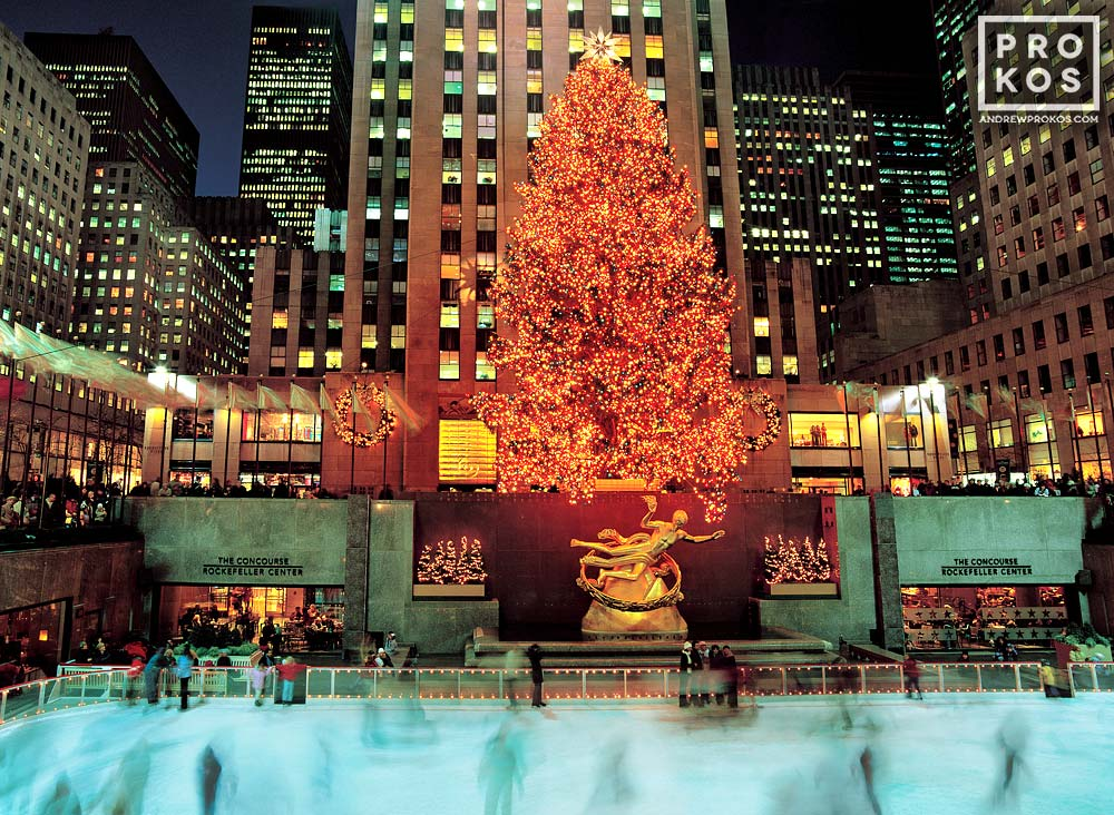 A long-exposure photo of the ice skaters under the lighted Christmas tree at Rockefeller Center, New York City