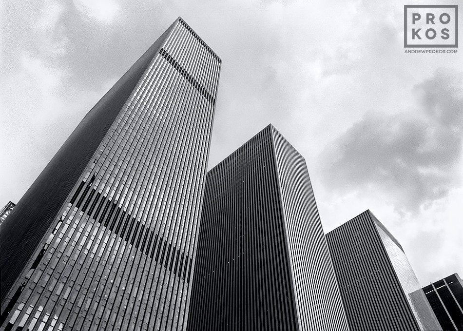 A black and white architectural photo of the skyscrapers of Rockefeller Center along Avenue of the Americas, NYC. They are (from left to right) the Exxon Building, The McGraw Hill Building and the Celanese Building