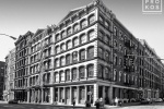 A black and white photo of the classic loft buildings at the intersection of Broome and Wooster streets in Soho, New York City