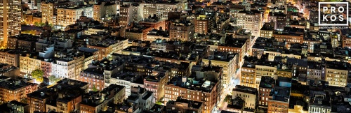 A long-exposure panoramic cityscape photo of the rooftops of SoHo New York City as seen from above at night.
