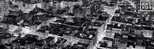 A panoramic fine art photo of the rooftops of Soho New York City at night in black and white.