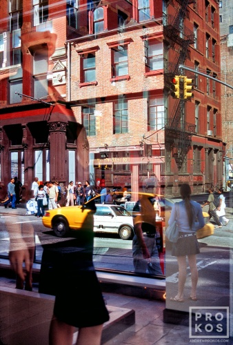 A street scene photo of the reflections of passersby in a Soho dress shop window, New York City