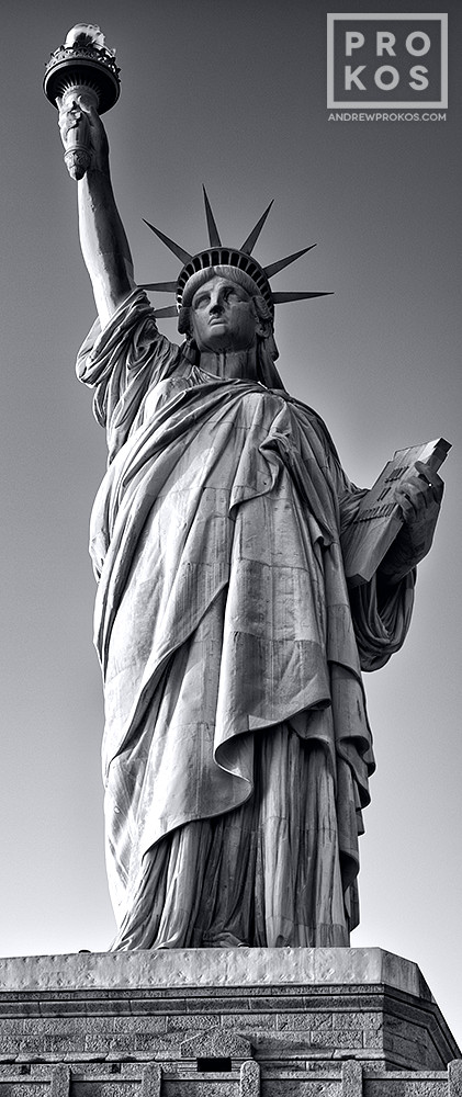 A vertical panoramic view of the Statue of Liberty in black and white, New York City.