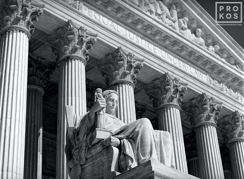 A black and white architectural photo of the facade of the US Supreme Court with the Contemplation of Justice statue in the foreground, Washington DC