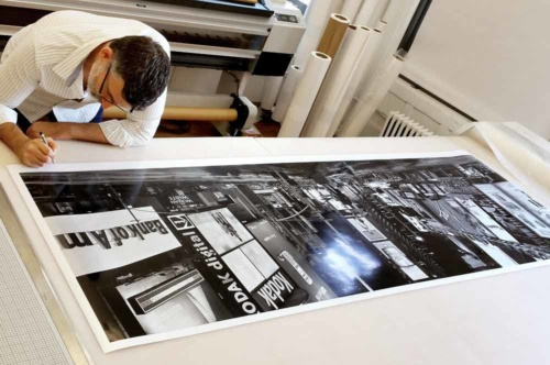 "Andrew Prokos signing a 90"" black and white limited edition print of ""Panoramic View of Times Square at Night"""