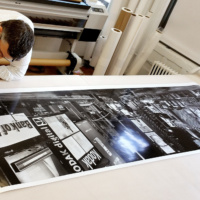 "Andrew Prokos with a 90 inch print of ""Panoramic View of Times Square at Night"""