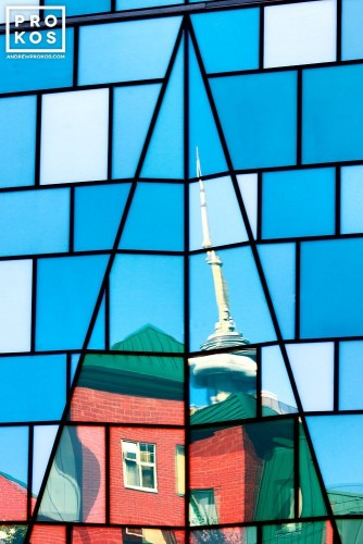 An architectural photo of CN Tower reflected on the glass facade of a Fashion District building, Toronto, Canada