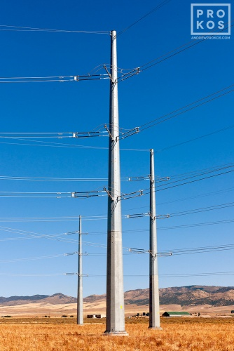 A photo of a group of steel electricity transmission towers set in a sparse Southern Idaho landscape