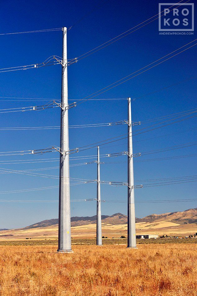 A landscape photo of a group of steel electricity transmission towers set in a sparse Southern Idaho landscape