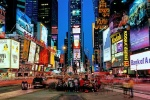 A panoramic cityscape photo of the signs of Times Square at dusk, New York City