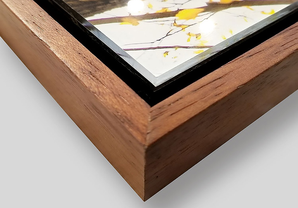 A detail of our acrylic float mount with solid walnut float frame