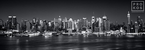 A black and white panoramic skyline photo of Midtown Manhattan at night from Weehawken, New Jersey.