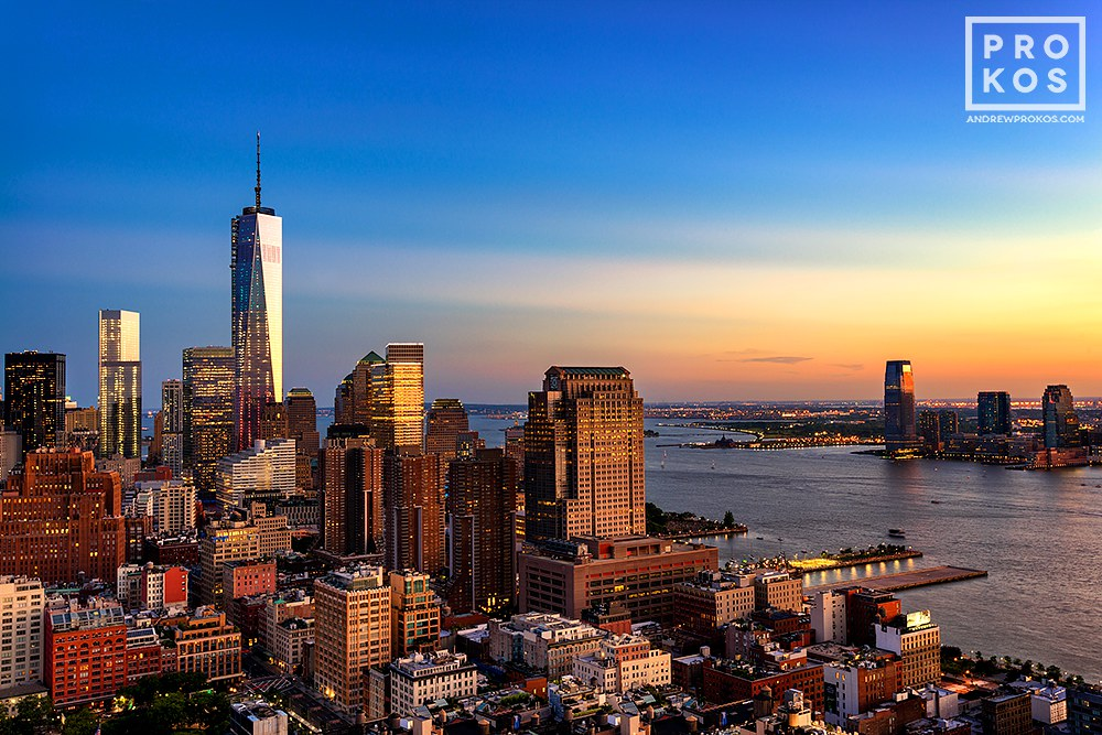 A cityscape photo of Lower Manhattan, World Trade Center, Hudson River, and New Jersey at dusk.