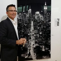 Photographer Andrew Prokos with one of his black and white photographs in the Inaugural Exhibition of 70 South Gallery